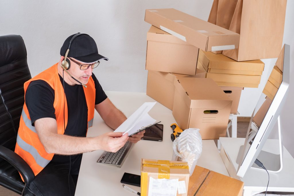 Man with boxes filling in paperwork